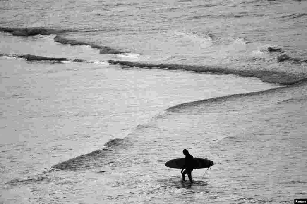 ទេសចរ ម្នាក់អោបក្តារមួយនៅមហាសមុទ្របន្ទាប់ពីឆ្នេរ Bondi Beach ត្រូវបានបើកឲ្យចូលវិញបន្ទាប់ពីបានបិទអស់រយៈពេលប្រាំសប្តាហ៍ក្នុងទីក្រុងស៊ីដនីប្រទេសអូស្ត្រាលី។