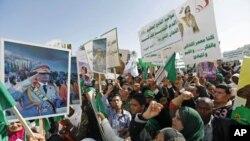 ພວກເດີນຂະບວນ ສະໜັບສະໜຸນລັດຖະບານລີເບຍ ຖືຮູບທ່ານ Moamma Gadhafi ໃນລະຫວ່າງ ການໂຮມຊຸມ ທີ່ນະຄອນຫຼວງ ຕຣີໂປລີ (17 ກຸມພາ 2011)