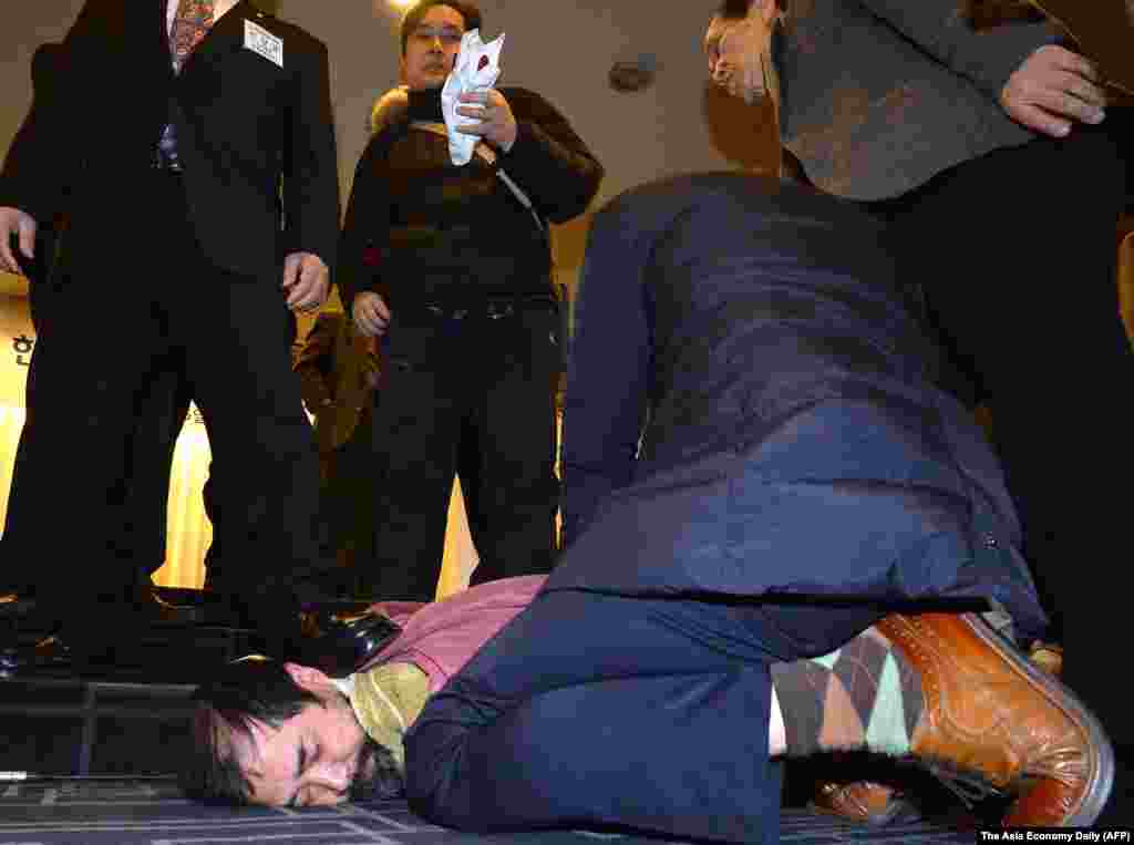 A man (bottom center) who attacked U.S. ambassador to South Korea Mark Lippert is detained by police at the Sejong Cultural Institute in Seoul, March 5, 2015.