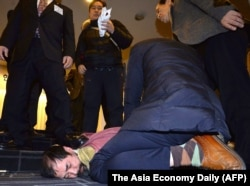 A man, bottom center, who attacked U.S. ambassador to South Korea Mark Lippert, is detained by police at the Sejong Cultural Institute in Seoul, March 5, 2015.