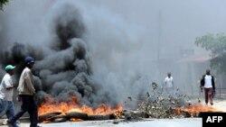 Un habitant de Lusaka passe devant des pneus en feu, Zambie, le 12 janvier 2018