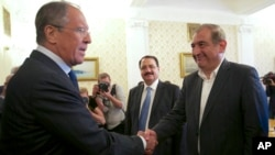 Russian Foreign Minister Sergei Lavrov, left, greets Syrian Deputy Prime Minister Qadri Jamil, right, in Moscow, Russia, July 22, 2013.