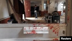 Blood stains a door following a twin bombing inside a mosque in Benghazi, Libya, Feb. 9, 2018.