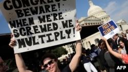 美國政府關閉而停工的聯邦僱員在國會前舉牌抗議。