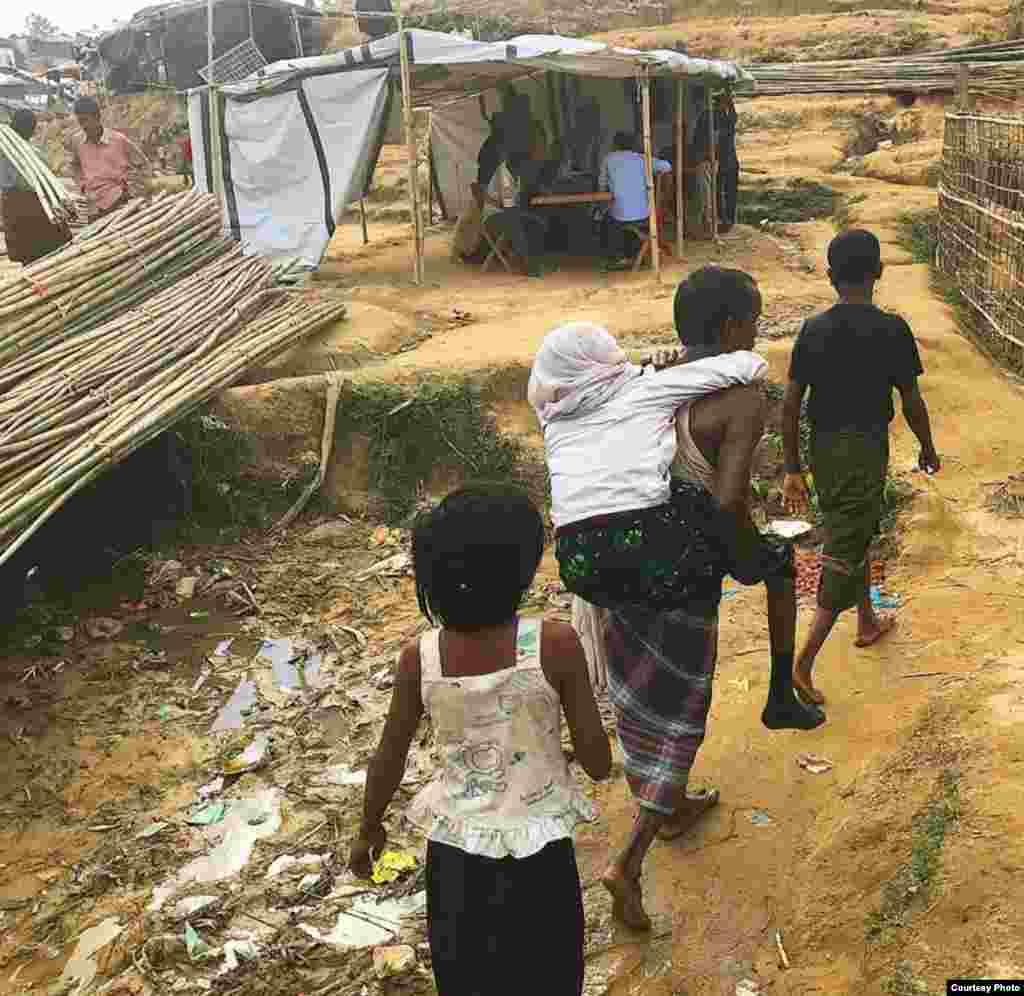 Rohingya refugees walk along a litter-strewn path next to makeshift tents at a camp in Bangladesh. (Photo courtesy of Dr. Imran Akbar)