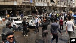 Civilians and security forces inspect the scene of a car bomb explosion in Karrada neighborhood, Baghdad, Iraq, May 9, 2015.