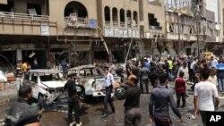 Pasukan keamanan dan warga Irak memeriksa lokasi serangan bom mobil di distrik Karrada, Baghdad (foto: dok).