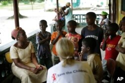 Carolyn Miles (foreground), CEO of Save the Children, listens to orphans at a Liberian government-run facility in Unification town, Oct. 3, 2014.