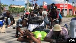 Para jurnalis Haiti bertiarap untuk menghindari terkena tembakan pada saat bentrokan antara polisi dan demonstran anti pemerintah di Port-au-Prince, Haiti, Kamis (31/10).