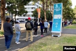 FILE - People wait in line outside a coronavirus disease (COVID-19) vaccination center at Sydney Olympic Park in Sydney, Australia, June 23, 2021.