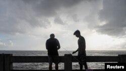 Alex Rodríguez y su primo Javier Rodríguez pescan desde el muelle del puente North Skyway mientras nubes oscuras se ciernen sobre el canal de la Bahía de Tampa antes de la tormenta tropical Elsa, en St. Petersburg, Florida, el 5 de julio de 2021. REUTERS