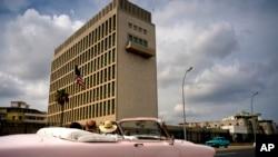 Para turis mengendarai mobil klasik melintas di depan gedung Kedutaan Besar AS di Havana, Kuba, 18 Maret 2019.
