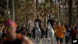 Mounted police patrol on horses as people exercise on a seafront promenade in Barcelona, Spain, Sunday, May 3, 2020.