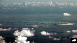 FILE - In this Monday, May 11, 2015, file photo, This photo taken through a glass window of a military plane shows China's alleged on-going reclamation of the Spratly Islands in the South China Sea.
