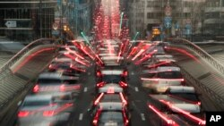 FILE - In this slow-shutter zoom effect photo taken Dec. 12, 2018, commuters are backed up in traffic during the morning rush hour in Brussels, a city that regularly experiences pollution alert warnings.