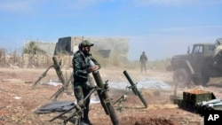 FILE - In this photo released by the Syrian official news agency SANA, Syrian army soldiers prepare to launch a mortar towards insurgents in the village of Kfar Nabuda, in the countryside of Hama province, Syria, May 11, 2019.