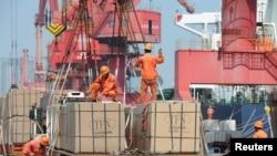 2019年6月7日,工人在中国江苏路连云港市的一个港口起重机上装载货物。(资料照)