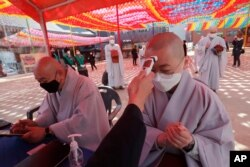 A Buddhist monk wearing a face mask is checked his temperature by a Korea Red Cross official to donate blood due to the shortage of blood donators amid the rapid spread of the new coronavirus at the Jogyesa temple in Seoul, March 24, 2020.