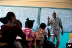 Students listen to school Director Jean Marc Charles at the Lycée school, which reopened about a week earlier than other schools in Petion-Ville, Haiti, Nov. 28, 2019.