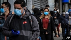 People in Brooklyn's Sunset Park, a neighborhood with one of the city's largest Mexican and Hispanic community, wear masks to help stop the spread of coronavirus while waiting in line to enter a store, Tuesday May 5, 2020, in New York. A poll found…