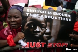 FILE - A woman holds a sign during a protest demanding the release of abducted secondary school girls from the remote village of Chibok, in Lagos, May 5, 2014.