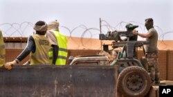 Les commandos de la force française Barkhane montent une mitrailleuse sur une camionnette camouflée alors que des travailleurs maliens passent avant de partir en mission depuis leur base de Gao, au Mali, le undi 7 juin 2021.