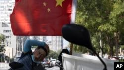 北京街头一名快递员在电动车旁休息。(2020年9月2日)