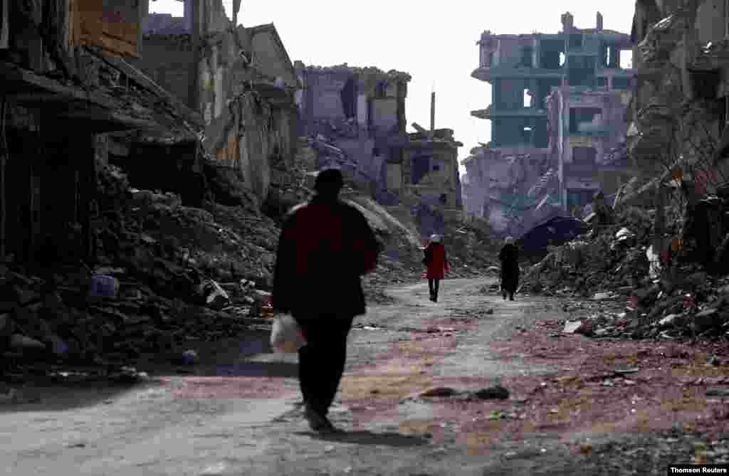 시라아 다마스쿠스의 '야묵(Yarmouk)' 팔레스타인 난민 캠프의 부서진 건물들 사이로 사람들이 걷고 있다.