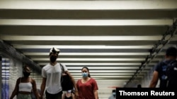 People wear masks as they pass through a pedestrian subway as cases of the infectious coronavirus Delta variant continue to rise in New York City, New York