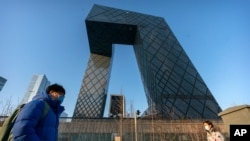 FILE- In this Thursday, Feb. 4, 2021 file photo, people wearing face masks to protect against the spread of the coronavirus, walk past the CCTV Headquarters building, the home of Chinese state-run television network CCTV and its overseas arm CGTN,…