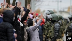 Demonstrators stand with their hands up in front of riot police line during an opposition rally to protest the official presidential election results in Minsk, Belarus, Nov. 1, 2020.