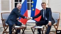 Le président français Emmanuel Macron, à droite, serre la main du président russe Vladimir Poutine à l'issue de leur rencontre au fort de Bregancon à Bormes-les-Mimosas, dans le sud de la France, le 19 août 2019.