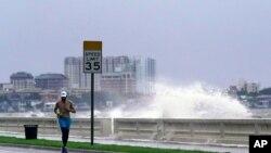Un corredor se abre paso a lo largo de Bayshore Boulevard, en Tampa, Florida, mientras una ola rompe sobre un malecón, durante las secuelas de la tormenta tropical Elsa el miércoles 7 de julio de 2021.