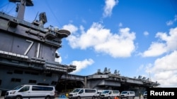 FILE - Seabees coordinate transportation of U.S. Navy sailors assigned to the aircraft carrier USS Theodore Roosevelt who have tested negative for coronavirus disease (COVID-19) to locations off base at Naval Base Guam, April 10, 2020.