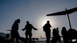 ທະຫານອາເມຣິກັນ ນຳເອົາຜູ້ຄົນໄປຂຶ້ນເຮືອບິນຂົນສົ່ງ ທີ່ສະໜາມບິນສາກົນຮາມິດ ກາໄຊ ໃນນະຄອນຫຼວງກາບູລ ເມື່ອວັນທີ 4 ສິງຫາ 2021. (US Air Force photo)