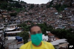 A man wears a mask to protect himself against the spread of the new coronavirus as he donates food for poor families in Turano favela, Rio de Janeiro, Brazil, April 15, 2020.
