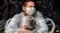A nurse and patient embrace in this cropped version of the image released by World Press Photo, April 15, 2021, by Mads Nissen, Politiken, Panos Pictures, which won the World Press Photo of the Year award.
