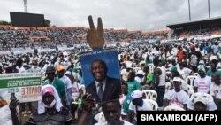 Un homme tient une pancarte représentant l'ancien président ivoirien Laurent Gbagbo lors d'un rassemblement contre la candidature à un 3e mandat du président Ouattara, le 10 octobre 2020 au stade Félix Houphouët-Boigny d'Abidjan.