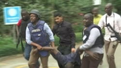 Kenya Police Carry Injured Man from Scene