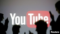 FILE - Silhouettes are seen in front of a Youtube logo, in this picture illustration taken in Zenica, Oct. 29, 2014.