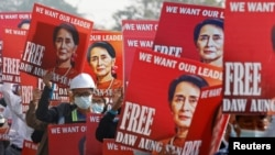 Demonstrators hold placards with the image of Aung San Suu Kyi during a protest against the military coup, in Naypyitaw, Myanmar, Feb. 17, 2021.