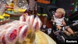 یک نوزاد به آبنبات ها و تنقلات در فروشگاهی در نیویورک نگاه می کند. آرشیو، ۱۵ ژوئیه ۲۰۱۵
