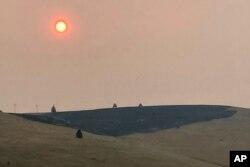 El humo oscurece el aire y el sol sobre una ladera quemada por un incendio forestal reciente, en Missoula, Montana, el domingo 18 de julio de 2021.