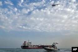 FILE - A speedboat and a helicopter of the Iran's Revolutionary Guard move around a British-flagged oil tanker Stena Impero, which was seized by the Guard, in the Iranian port of Bandar Abbas, July 21, 2019.