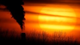 In this Monday, Feb. 1, 2021 file photo, emissions from a coal-fired power plant are silhouetted against the setting sun in Independence, Mo. A United Nations report released on Thursday, Feb. 18, 2021 says humans are making Earth a broken and increasingly unlivable planet throug