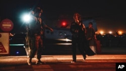 FILE - A Marine escorts a Department of State employee to be processed for evacuation, at Hamid Karzai International Airport, in Kabul, Afghanistan, Aug. 15, 2021. The U.N. also evacuated about 100 staff, moving them to Kazakhstan on Aug. 18, 2021.