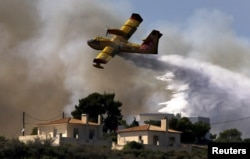 A firefighting plane drops water over a fire near holiday homes in Costa village in the Argolida region, in Southeastern Greece during a developing wild fire, July 20, 2015.