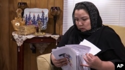 In this image from video, Zumret Dawut, a Uighur from China's far western Xinjiang region, holds documents she brought with her, at her new home in Woodbridge, Va., on Monday, June 15, 2020. Dawut says in China, she was forcibly sterilized for…