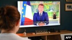 Une famille française regarde à Lille la déclaration du président Emmanuel Macron, faite depuis le palais de l'Élysée à Paris, sur la pandémie de COVID-19, le 14 juin 2020.