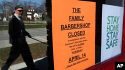 A pedestrian walks by The Family Barbershop, closed due to a Gov. Gretchen Whitmer executive order, in Grosse Pointe Woods, Mich., April 2, 2020.